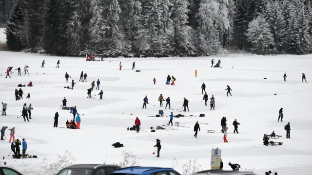 People ice-skate and play hockey on the frozen lake Spitzingsee, near the resort town of Schliersee