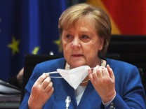 German Chancellor Merkel takes off her face mask as she prepares to lead the weekly cabinet meeting, in Berlin