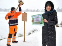 Weßling: See - Thomas Becker und Astrid Kahle bringen Hinweisschilder an