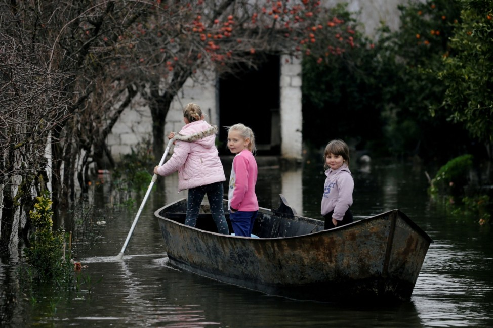 Children use a boat at a flooded area in Obot village