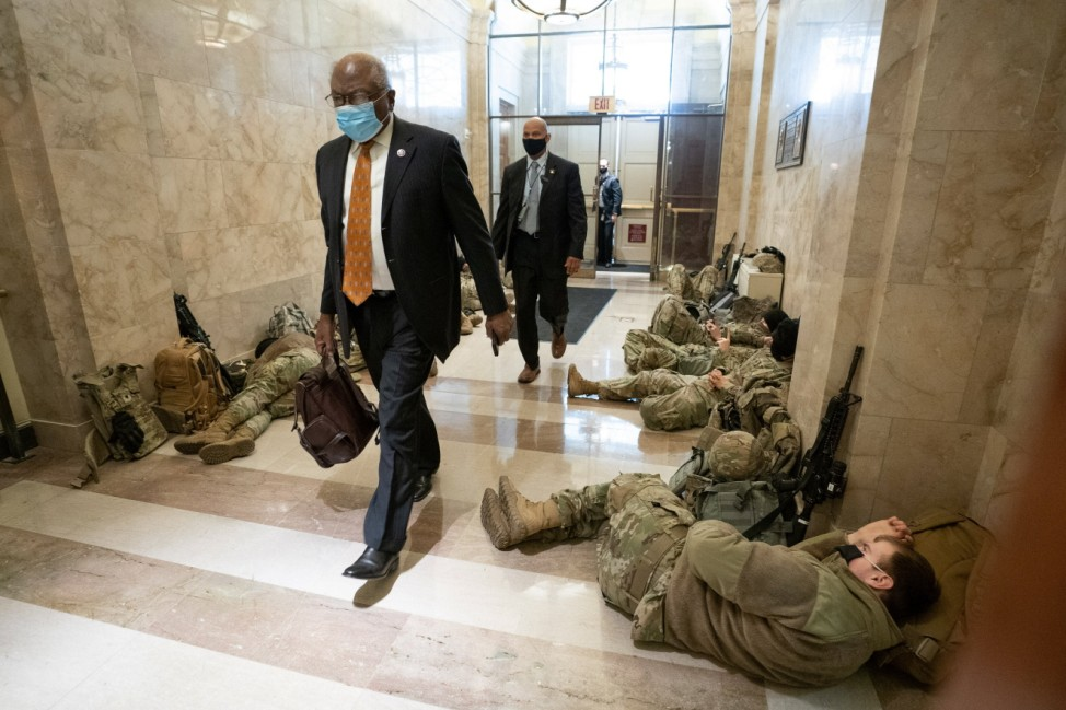 House Majority Whip James Clyburn walks past sleeping members of the National Guard inside the U.S. Capitol as security