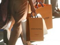 Frauen tragen Papiertüten von Louis Vuitton in der Fußgängerzone und Einkaufsstraße Kaufingerstraße ind der Innenstadt v