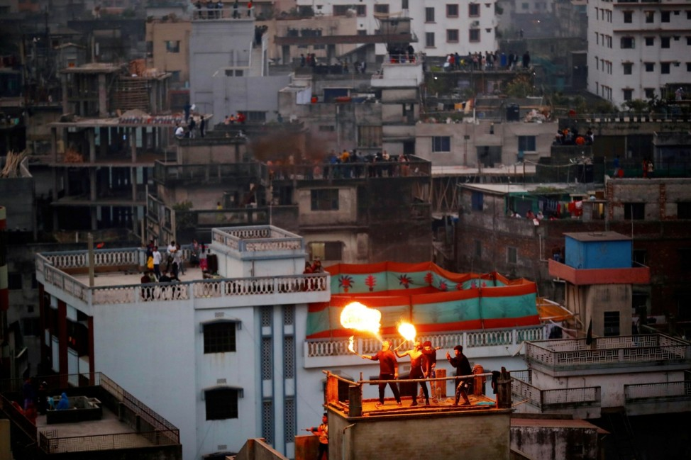 People perform fire breathing on their rooftop during Sakrain festival in Dhaka