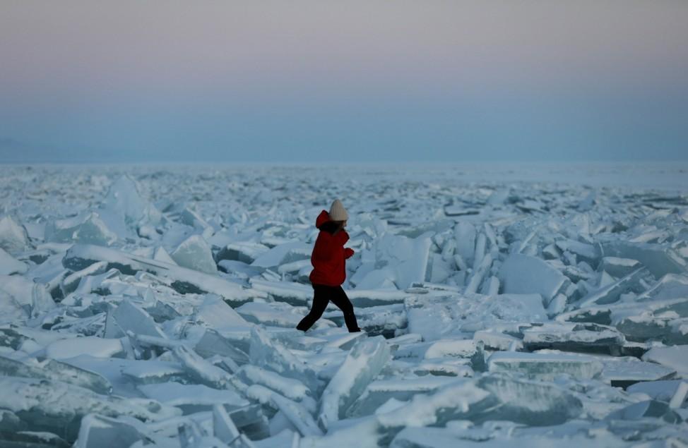 A woman walks through chunks of ice on the frozen Kapchagay reservoir outside Almaty