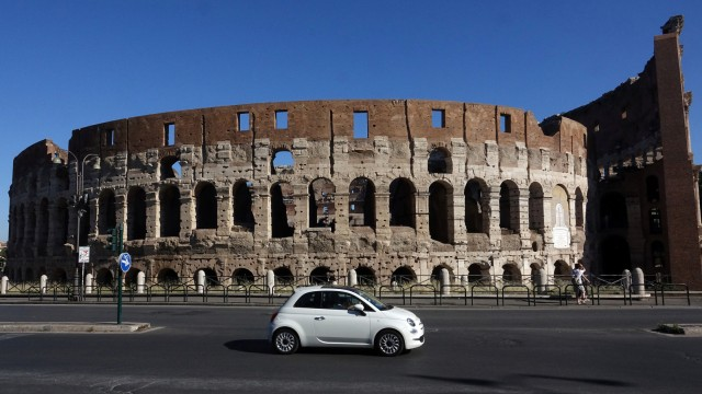 A Fiat 500 is seen in front of the ancient Colosseum in Rome