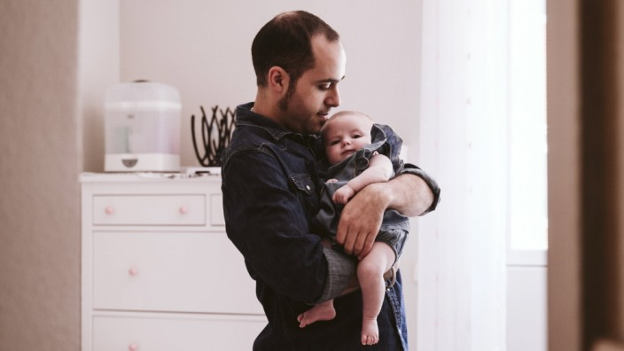 Father carrying cute baby girl in living room at home model released Symbolfoto EBBF00211