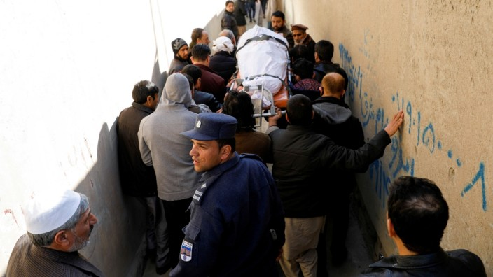 Relatives carry the body of female judge shot dead by unknown gunmen in Kabul