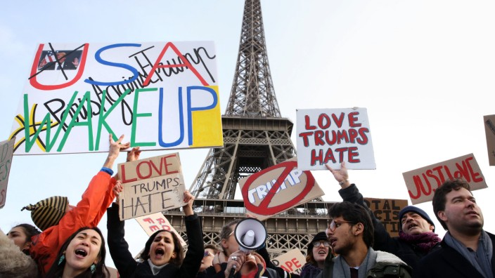 Bilder des Tages Demonstrators hold placards and chant slogans in front of the Eiffel Tower during a