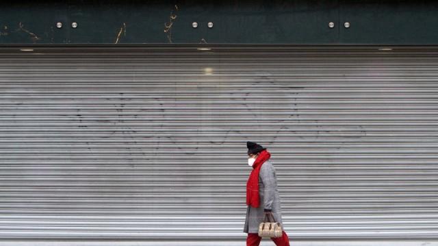 Eine Frau mit Maske geht an einer mit Rolltor verschlossenen Filiale der Modekette Primark in der Einkaufsstraße und Fu
