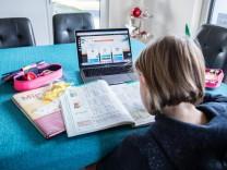 Bamberg, Deutschland 04. Januar 2021: Ein Kind sitzt an einem Tisch in einer Wohnung auf dem ein aufgeklappter Laptop mi