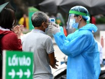 Corona in Vietnam: Temperaturmessung bei einem Mann