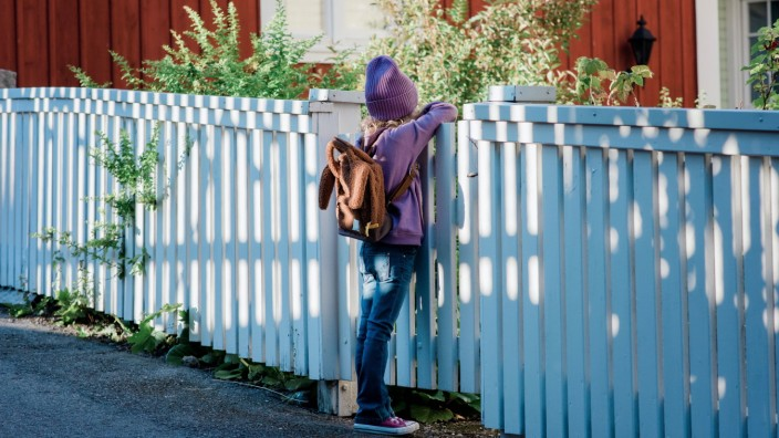 young girl leaning on a fence looking into the distance waiting Norrtälje, Stockholm County, Sweden PUBLICATIONxINxGERxS