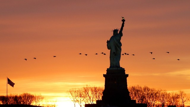 The sun rises behind the Statue of Liberty from Liberty State Park in Jersey City, New Jersey on Monday, January 11, 20