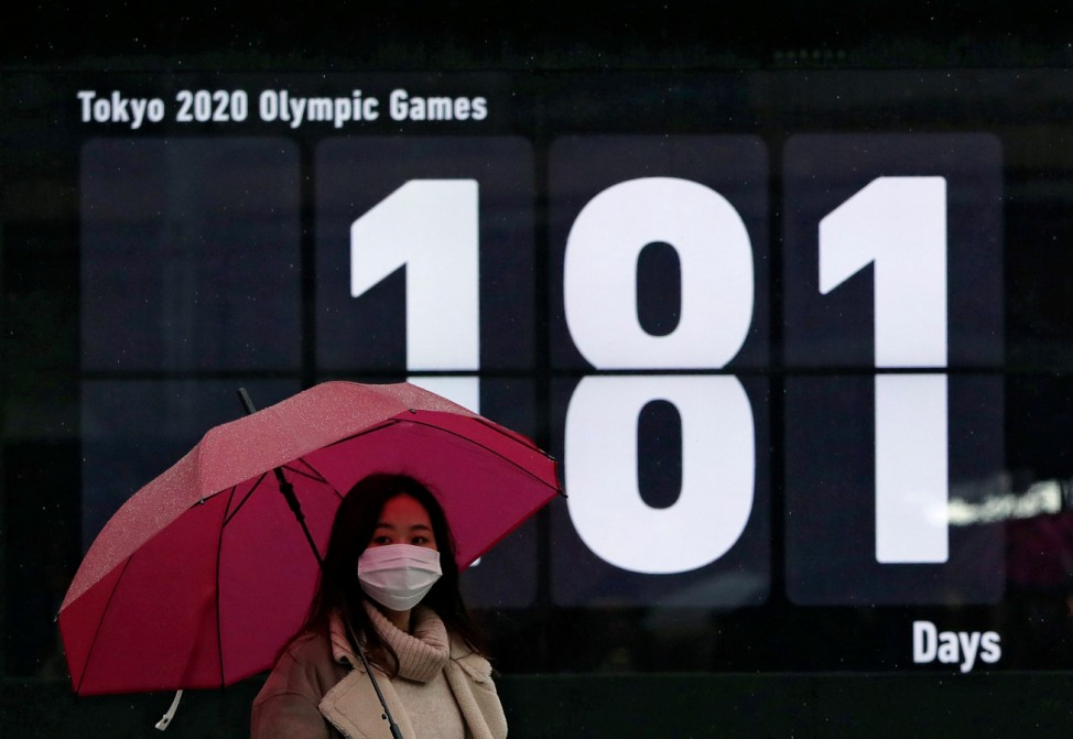 A passerby wearing a protective face masks walks past a screen showing a countdown of the days to the Tokyo 2020 Olympic Games, amid the coronavirus disease (COVID-19) outbreak in Tokyo