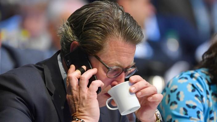 Andreas SCHEUER (Bundesverkehrsminister), telefoniert mit Smartphone und trinkt aus einer Tasse, Einzelbild,angeschnitte