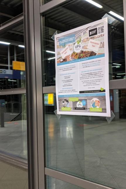 Unterföhring: Ein Plakat am Unterföhringer Bahnhofsgebäude weist auf den geplanten Unverpackt-Laden hin.