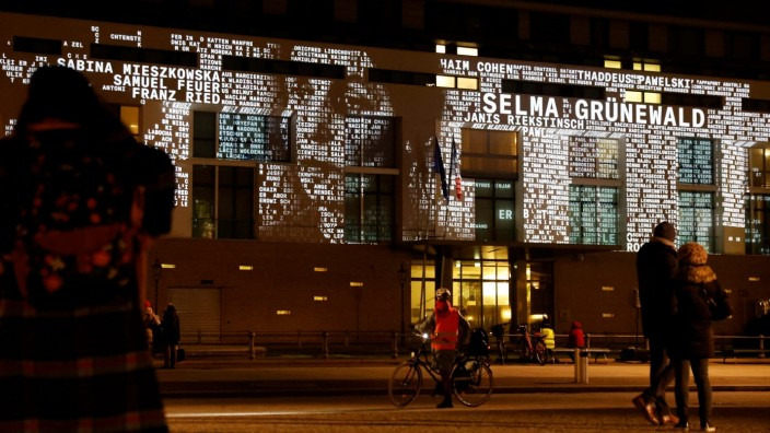 People watch at a light installation called #everynamecounts projecting names of victims of the Nazi regime in Berlin