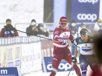 Alexander Bolshunov of Russia (red) slashing Joni Mäki of Finland with his stick in the final meters of the men s Cross