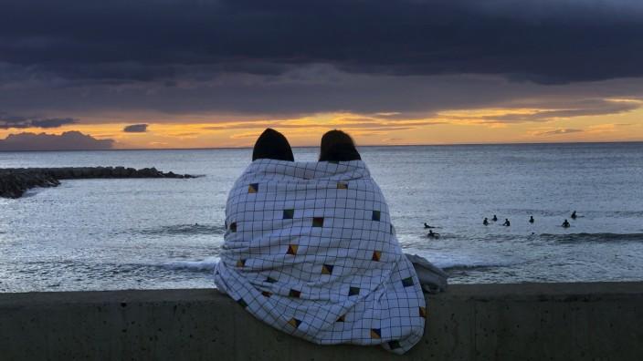 Paar während eines Sonnenuntergangs am Strand