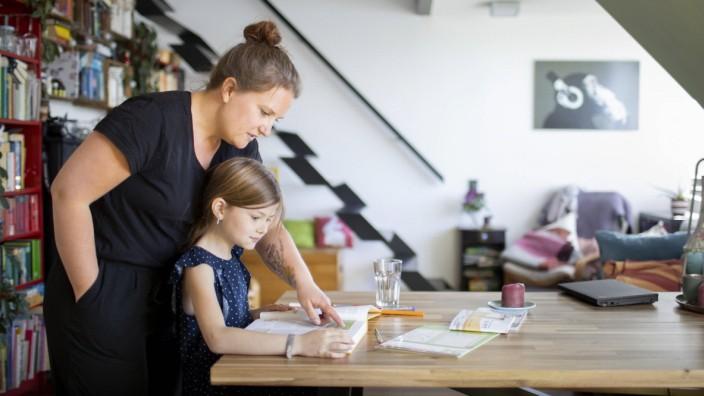 Homeschooling: Mutter hilft Kind bei den Hausaufgaben