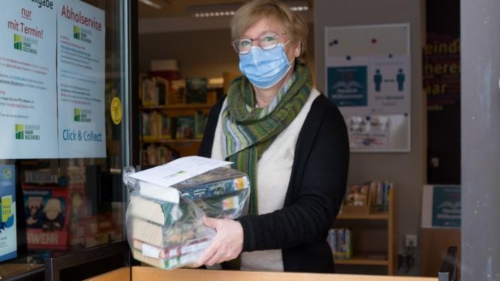Ingrid Dierolf, Mitarbeiterin der Gemeindebücherei Haar, legt Bücher zur Abholung am Eingang bereit.