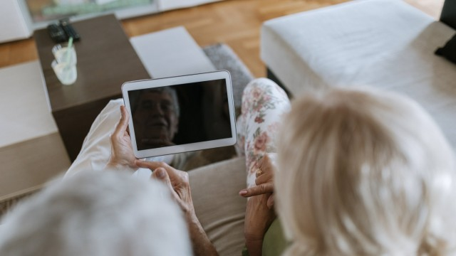 Senior couple at home sitting on couch sharing tablet model released Symbolfoto property released PU