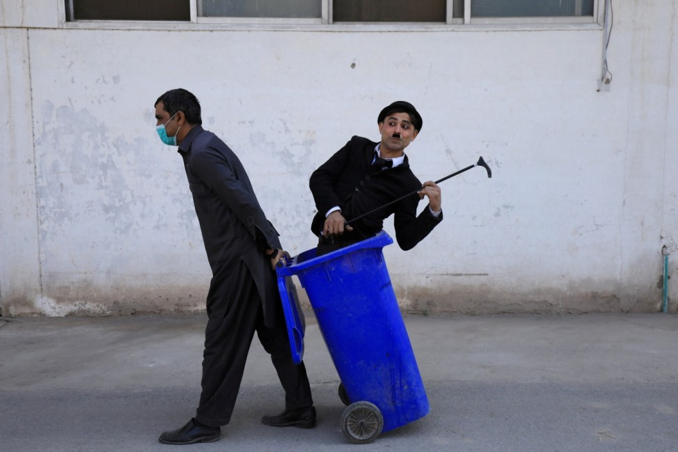 Usman Khan, 29, dressed up as Charlie Chaplin, performs along the street in Peshawar
