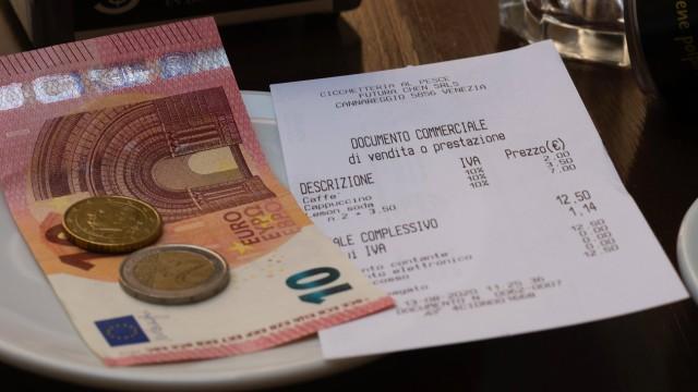 Geld liegt auf einem Teller neben einem Kassenzettel an einer Bar. Venedig, Venezien, Italien. In den Gassen der Lagunen