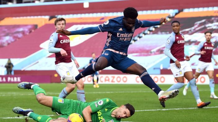 Aston Villa v Arsenal - Premier League - Villa Park Arsenal s Bukayo Saka jumps over Aston Villa goalkeeper Emiliano Ma