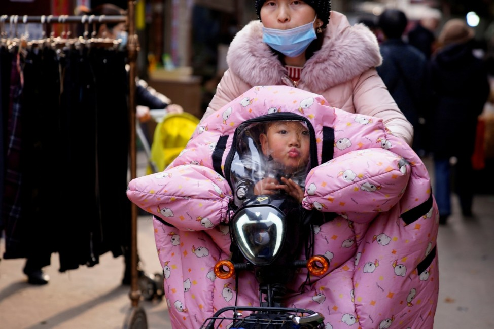 A woman wearing a face mask rides a bicycle with a child, following an outbreak of the coronavirus disease (COVID-19) in Wuhan