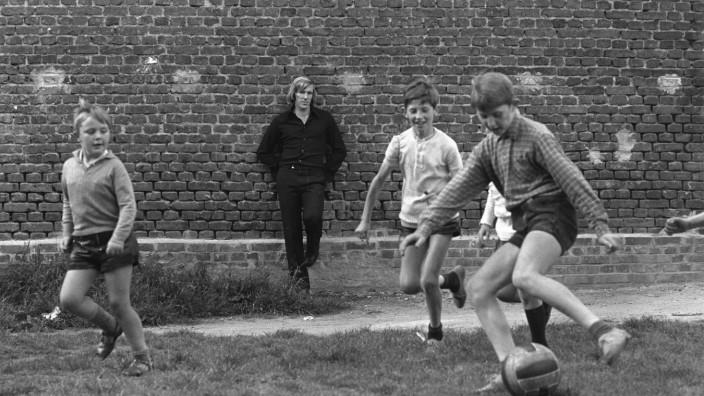 Fußball-Literatur: Hier träumt Günter Netzer im Juli 1971, damals schon mit kontrovers diskutierter Haarpracht, vermutlich von einfacheren Zeiten als Straßenfußballer.