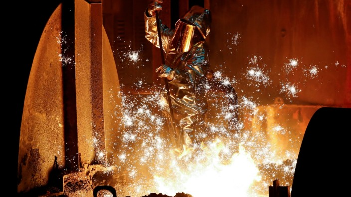 FILE PHOTO: A steel worker of Germany's industrial conglomerate ThyssenKrupp AG takes a sample of raw iron from a blast furnace at Europe's largest steel factory in Duisburg