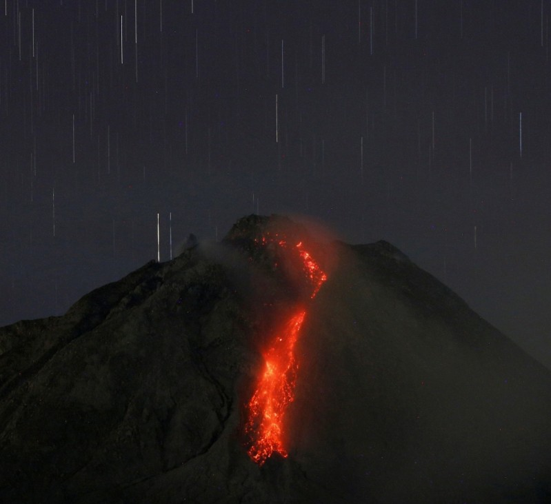 Hot lava flows from the top of Mount Sinabung volcano as seen from Tiga Kicat village in Karo