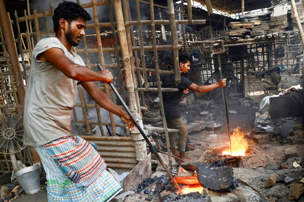 Bangladeshi laborers work at a factory where they make different machinery parts by melting metals, in Dhaka