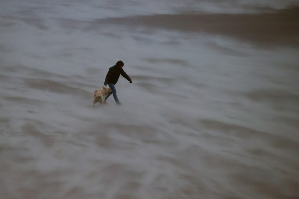 A man walks his dog along the beach in strong wind at New Brighton