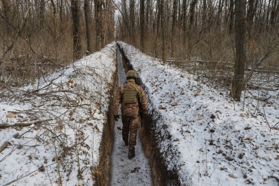 A Ukrainian service member walks along fighting positions near Avdiivka