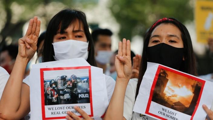 February 13, 2021, Bangkok, Thailand: Myanmar citizens wearing face masks make three-finger salute while holding placard