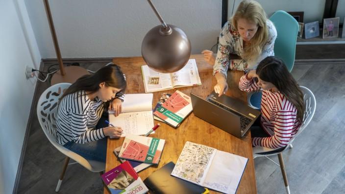 Homeschooling, während des Lockdowns im Januar 2021, Mutter hilft ihren beiden Töchtern, zuhause, beim lernen, mit Schul