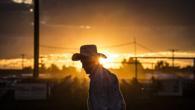 Aug 12, 2016 - Bozeman, Montana, USA - A rodeo clown interacts with the crowd at sunset during a Professional Rodeo Cowb