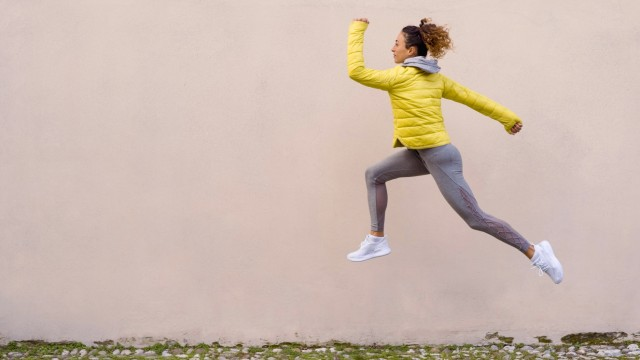 Athlete wearing hooded shirt running against pink wall model released Symbolfoto MAUF03684
