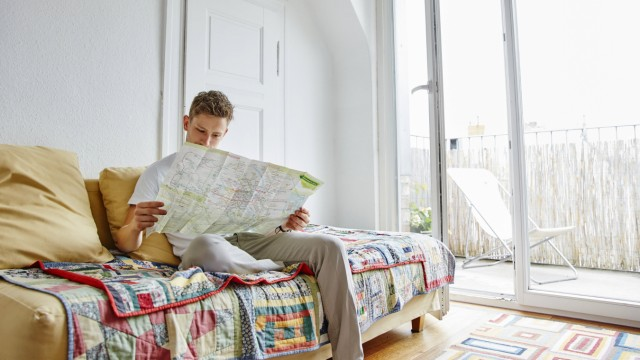 Young man sitting on couch at home reading map model released Symbolfoto property released PUBLICATI