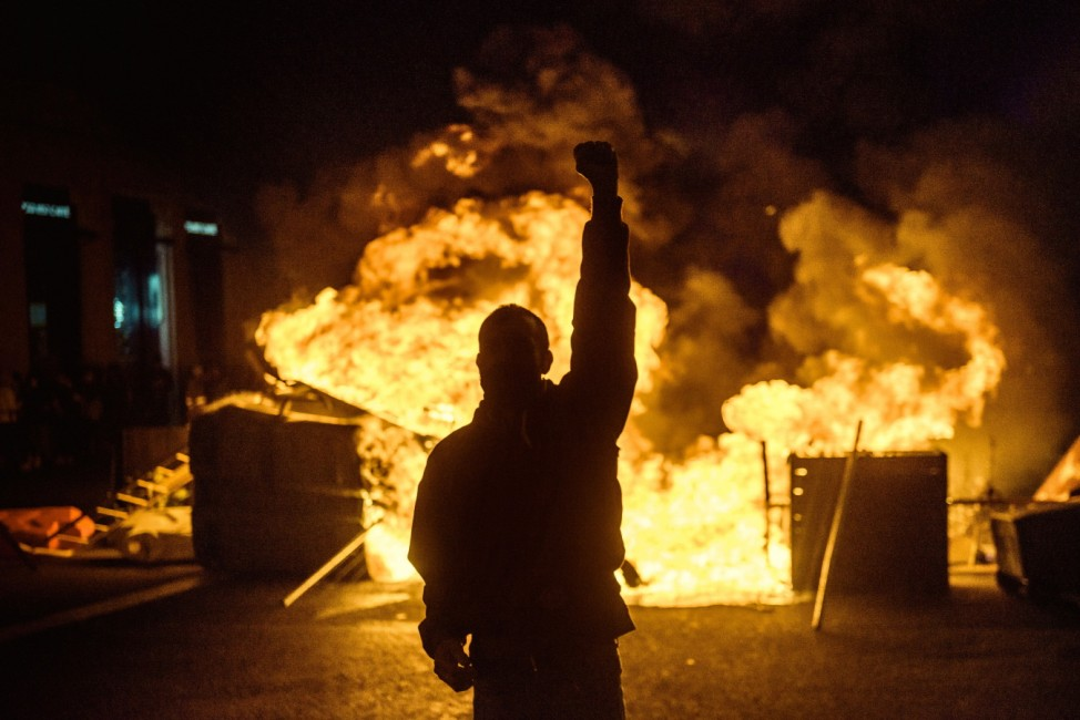 February 17, 2021, Barcelona, Catalonia, Spain: A protester poses for a photo in front of a burning barricade as a prote