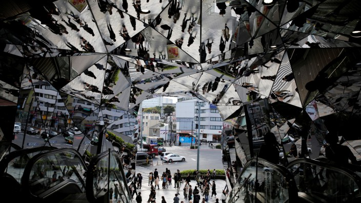 People are reflected in mirrors at an entrance to a department store in Tokyo