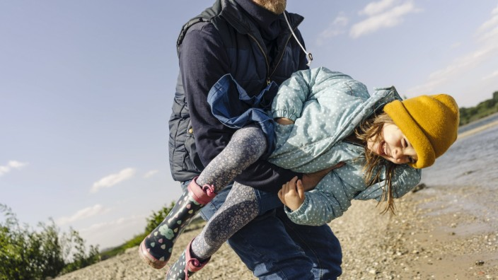 Father carrying daughter while enjoying near river bank model released Symbolfoto GUSF04457