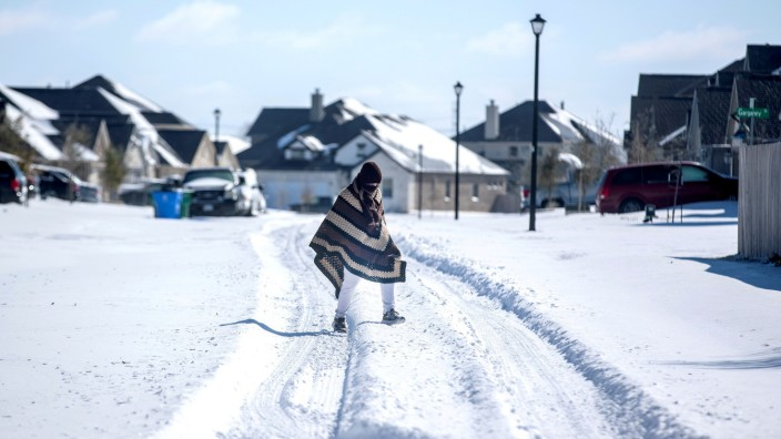 FILE PHOTO: A man walks to his friend's home in a neighborhood without electricity as snow covers the BlackHawk neighborhood in Pflugerville