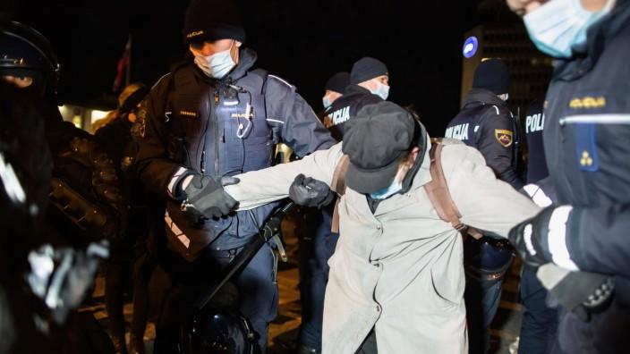 February 15, 2021, Ljubljana, Slovenia: Policemen arrest a woman during an anti-government protest in Ljubljana. The pr