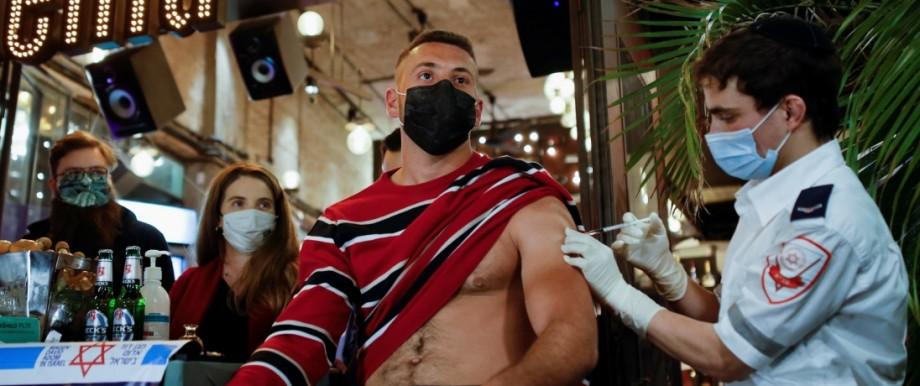 A man receives a vaccination against the coronavirus disease (COVID-19) as part of a Tel Aviv municipality initiative offering a free drink at a bar to residents getting the shot, in Tel Aviv