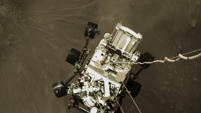 NASAâÄÖs Perseverance rover descends to touch down on Mars in a still image from a video camera aboard the descent stage