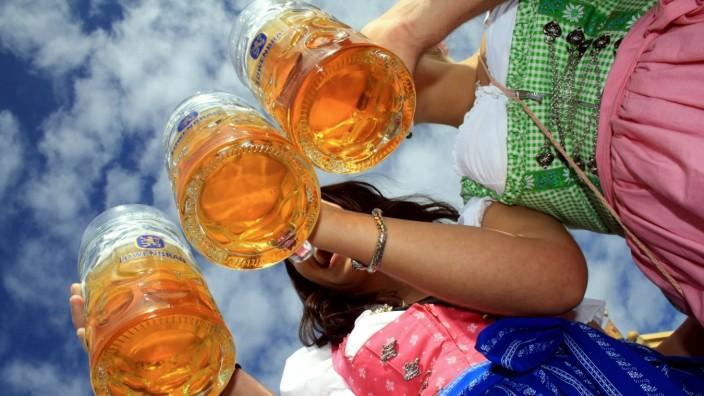 Auftakt Oktoberfest 2013: Wiesnbesucher in Tracht prosten sich mit einer Mass Bier zu; München, Oberbayern, Bayern, Deu