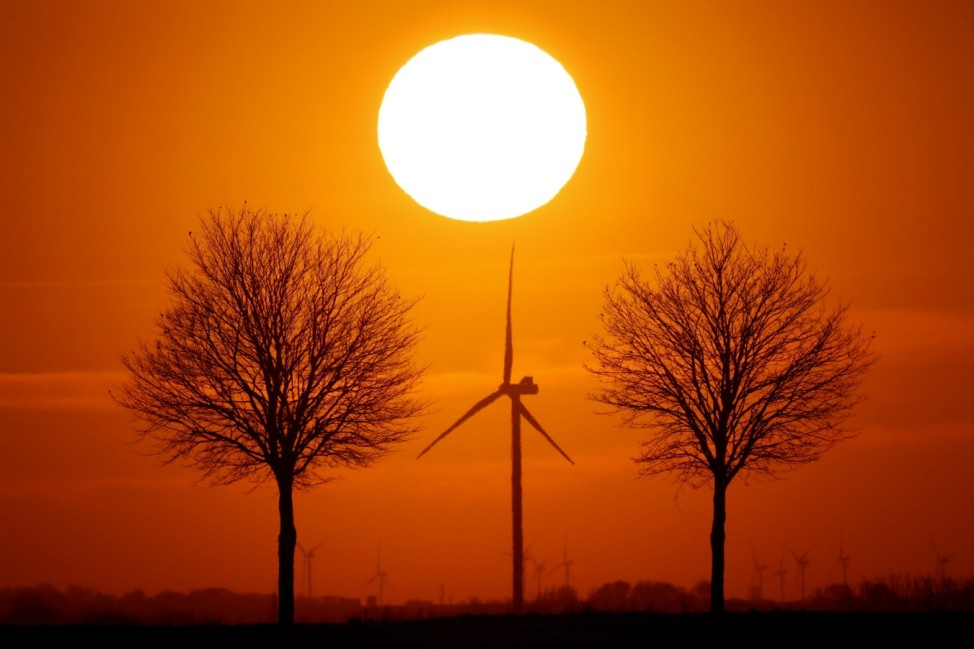 Power-generating windmill turbines are seen during sunset in Bourlon